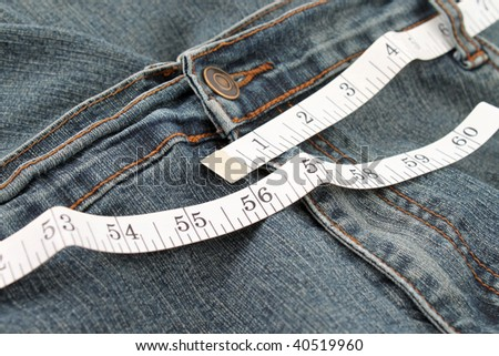 Measuring tape measuring an obese person's jeans waistline in inches - stock photo