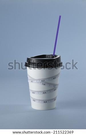 Measuring tape on a Paper cup - dieting concept image - stock photo