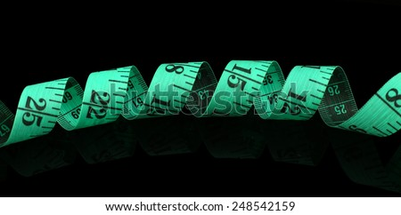 Measuring tape on black background - stock photo