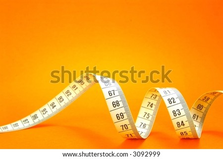 Measuring Tape On Orange Background - stock photo