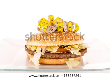 Measuring tape on the top of an appetizing hamburguer - diet concept - stock photo