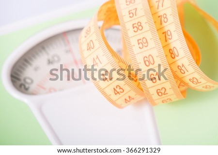 Measuring tape on top of scales.  - stock photo