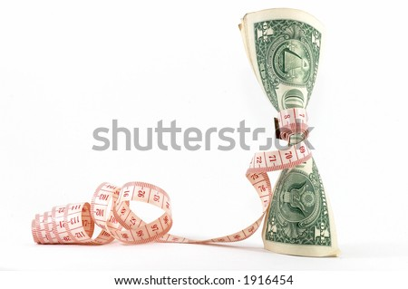 Measuring tape over money, budgeting, measure money, tight budget. Money upright. Could also signify expensive slimming treatment. Landscape orientation. - stock photo