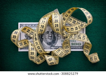 Measuring tape over one hundred dollars bill on green background. Close up. - stock photo