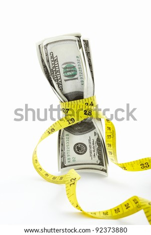 Measuring tape twining several US$100 bills over white background - stock photo