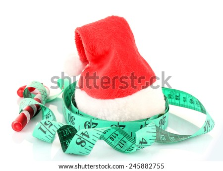 Measuring tape with Christmas decoration isolated on white - stock photo
