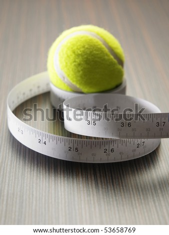 measuring tape with green tennis ball