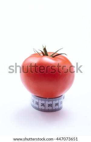 Measuring tape with tomato - stock photo