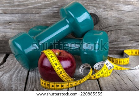 Measuring tape wrapped around a apple two dumbbells for fitness weight loss photo - stock photo