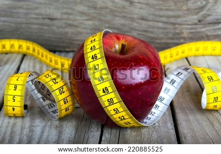 Measuring tape wrapped around a apple weight loss photo - stock photo