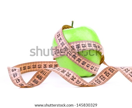 Measuring tape wrapped around a green apple. - stock photo