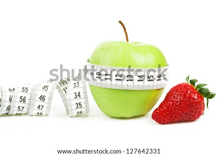 Measuring tape wrapped around a green apple and strawberry as a symbol of diet concept - stock photo