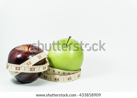 Measuring tape wrapped around two apples. Concept of diet. - stock photo