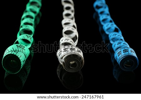 Measuring tapes on black background - stock photo