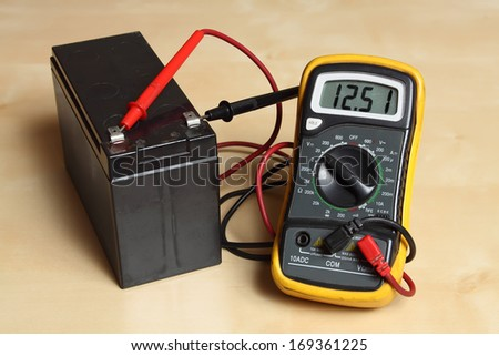 Measuring the battery voltage with a digital multimeter. - stock photo