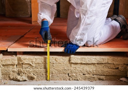 Measuring the thickness of thermal insulation - worker hands with tape measure - stock photo