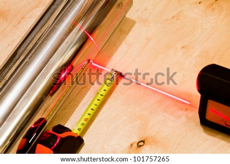 Measuring with tapemeasure tool and red laser beam - stock photo