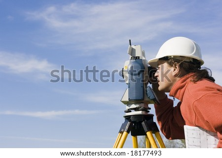 Measuring with theodolite - spring land surveying. - stock photo