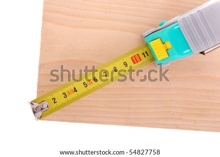 Measuring wood with yellow tape - stock photo