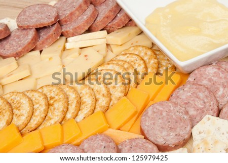meat and cheese tray including stone wheat crackers, wheat crackers, summer sausage, cheddar cheese, pepper jack cheese and a mustard sauce. - stock photo