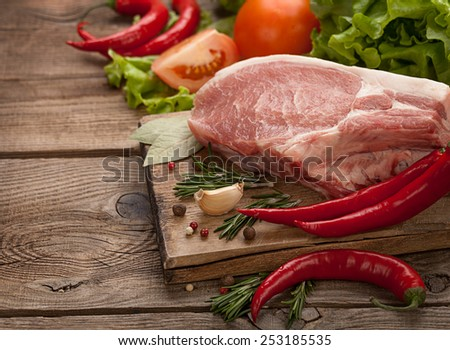 meat and pepper and spices on the table of the old boards