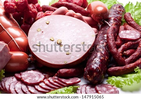 Meat and sausages on lettuce leaves. - stock photo
