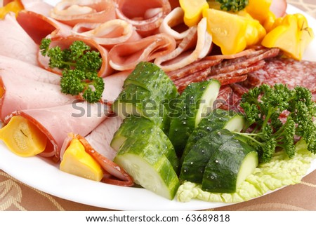 Meat and sausages with parsley and vegetables on white plate