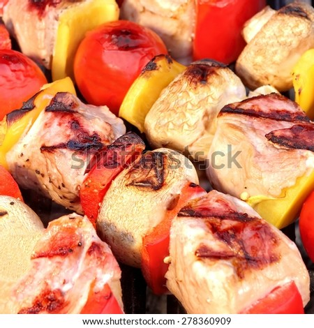 Meat And Vegetable Pork Kebabs On The Hot BBQ Grill Closeup. Flaming  Charcoal Grill In The Background. Snack For Outdoor Summer Barbecue Party. - stock photo