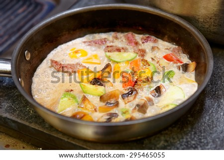 Meat and vegetables being cooked in cream