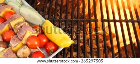 Meat And Vegetables Not Cooked Shish Kabobs On The Flaming Grill Close-up. Fire Of Flames In The Background. - stock photo