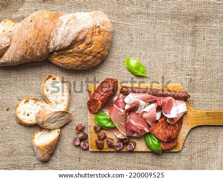 Meat appetizers selection and a loaf of rustic village bread on a rough wood board over a sackcloth background - stock photo