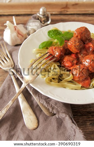 meat balls in tomato sauce Tagliatelle and basil on a wooden background