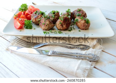Meat balls with parsley and tomatoes on a plate - stock photo