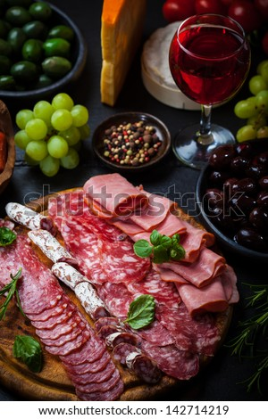 Meat catering platter with olives and red wine - stock photo