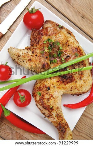 meat : chicken quarters garnished with red hot peppers on white plates over wooden table - stock photo