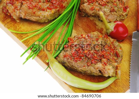 meat chops served with cutlery on wooden plate