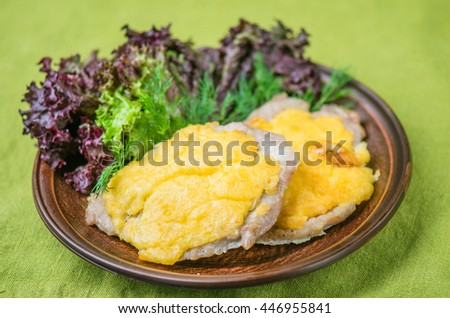 Meat chops with cheese and green salad in a brown plate on the table. Salad with fresh vegetables and roasted meat close up on a green background .  - stock photo