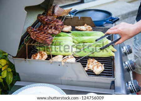 Meat cooking on a charcoal grill in a garden. - stock photo