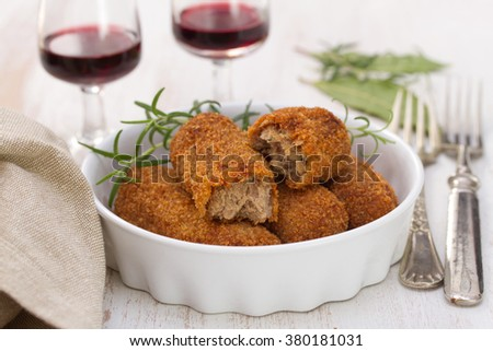 meat croquettes in dish and red wine on white background - stock photo