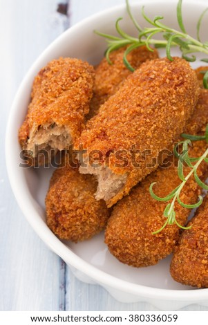 meat croquettes in white dish on blue wooden background - stock photo