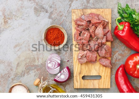 Meat cubes preparation. Raw ingredients for stew, goulash  or soup. Top view, blank space on the left side