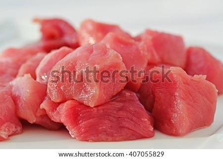 Meat cubes, raw red meat closeup (shallow dof) - stock photo