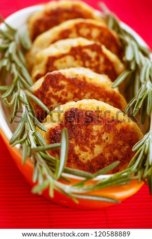 Meat cutlets with rosemary in bowl on red tablecloth. - stock photo