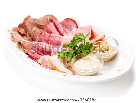 Meat delicatessen plate arranged with parsley and two sauce. Isolated on white