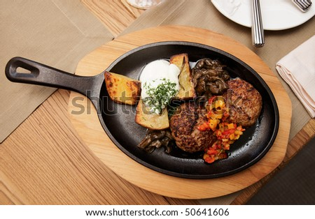 Meat dish - schnitzels, fried potato and garnish served on hot pan - stock photo
