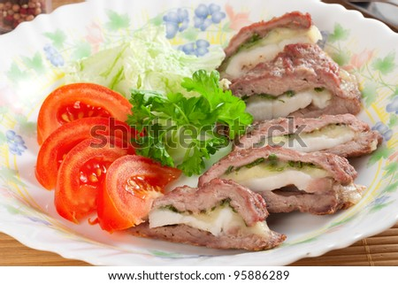 meat filled with bacon and cheese, tomatoes, parsley on plate