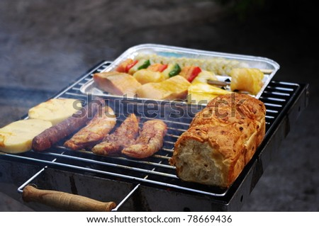 Meat, fish, bread and cheese on the barbecue grill.