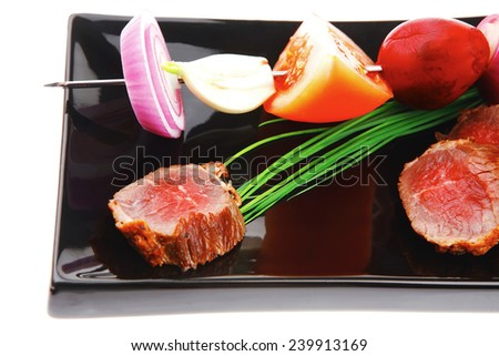 meat food : bbq meat served on black plate with vegetables on spit isolated on white background - stock photo