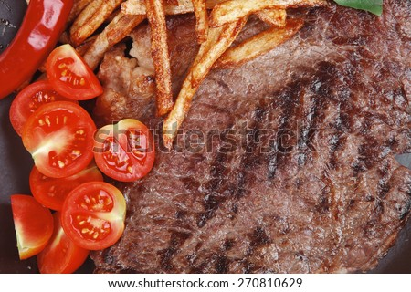 meat food : big grill beef steak on dark plate with red hot chili pepper and raw cherry tomato isolated on white background - stock photo