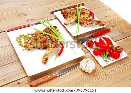 meat food : chicken legs garnished with green peas and and cutlery on white plates over wooden table - stock photo